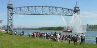 Photograph of Cape Cod Canal Rail Bridge with a crowd of people by the shoreline