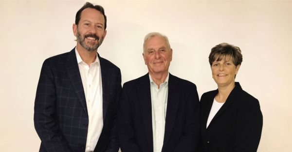 Photograph of Kinlin Grover President Mike Schlott with Ross Joly and Crystal Joly Weinert.