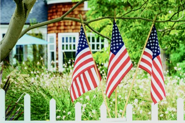 photograph of 3 american flags in front of a house with a white picket fence