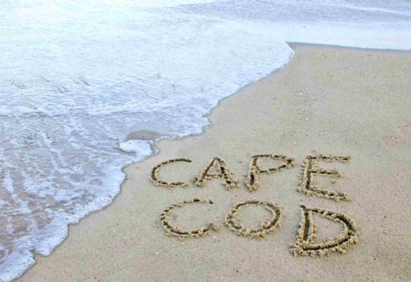 """Photograph of """"cape cod"""" written in the sand on the beach"""