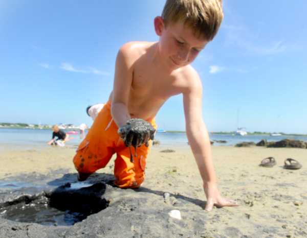 Image of young boy playing in the sand at Windmill Beach