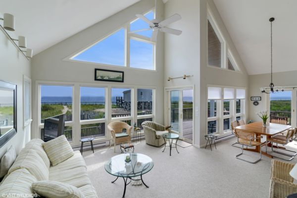 Photograph of Green Hill Ocean Retreat white living room with windows that share a view of the beach