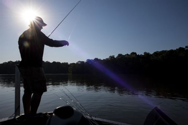 Photograph of silhouette of man fishing on the water
