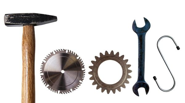 Photograph of 4 tools with a white background that spell out tools