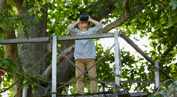 Photograph of a young boy on a bridge with binoculars looking at a view