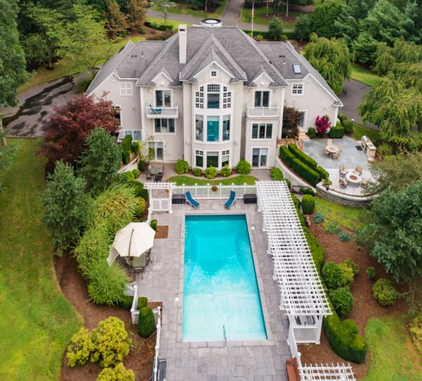 Photograph of a mansion with a pool in the front in Guilford, CT