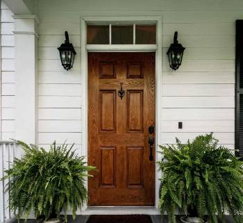 Photograph of the wood front door of a white home